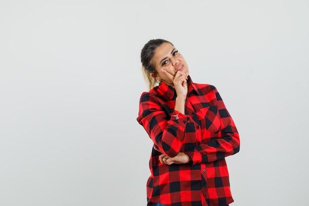 Junge dame im karierten hemd, das in denkender haltung steht und vernünftig aussieht