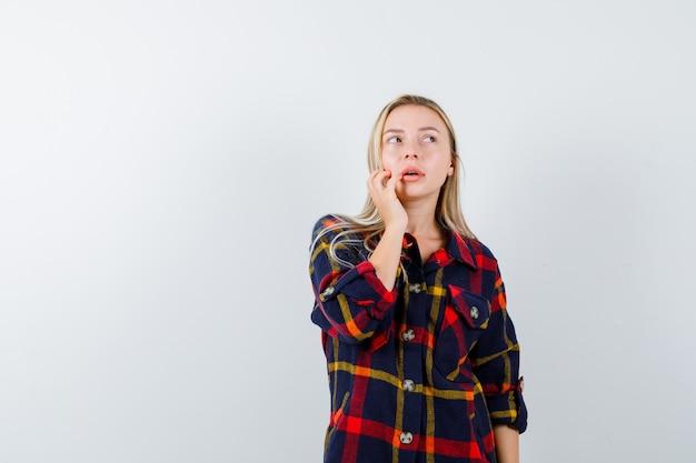 Junge dame im karierten hemd, das in der denkenden haltung steht, während sie aufschaut und unentschlossen schaut, vorderansicht.
