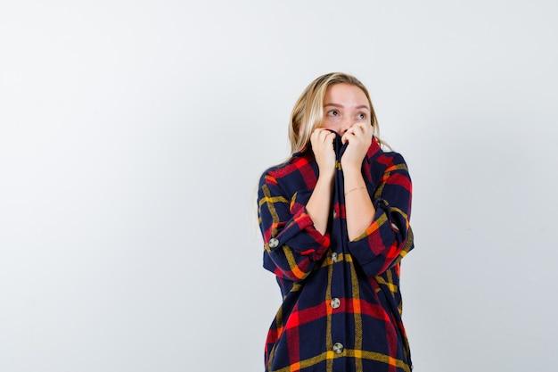 Junge dame im karierten hemd, das mund mit hemd bedeckt und ängstlich schaut, vorderansicht.