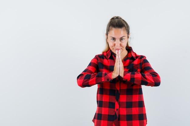 Junge dame im karierten hemd, das namaste geste zeigt und hoffnungsvoll aussieht