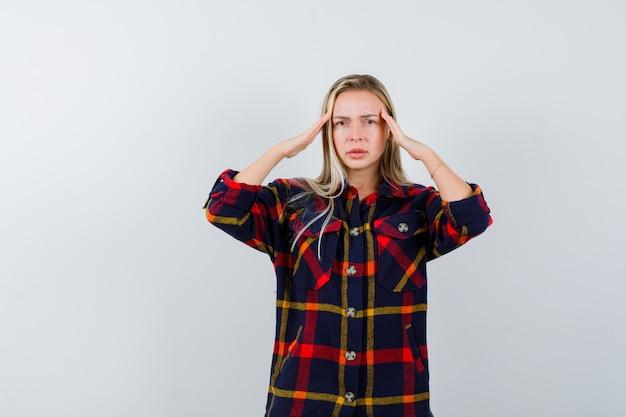 Junge dame im karierten hemd, das schläfen reibt und erschöpft aussieht, vorderansicht.