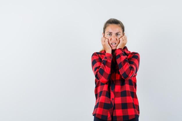 Junge dame im karierten hemd, die fäuste auf den wangen hält und erschrocken aussieht