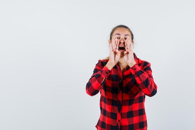 Junge dame im karierten hemd, die schreit oder geheimnis erzählt