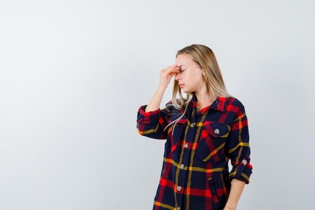Junge dame im karierten hemd reibt sich die stirn und sieht müde aus, vorderansicht.