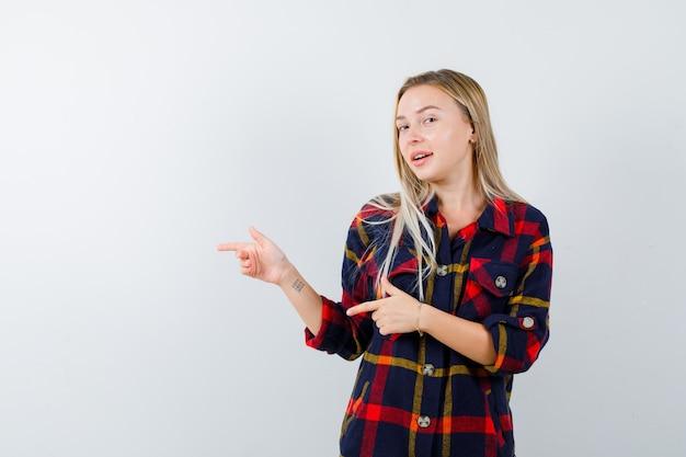 Junge dame im karierten hemd zeigt auf die linke seite und sieht glücklich aus, vorderansicht.