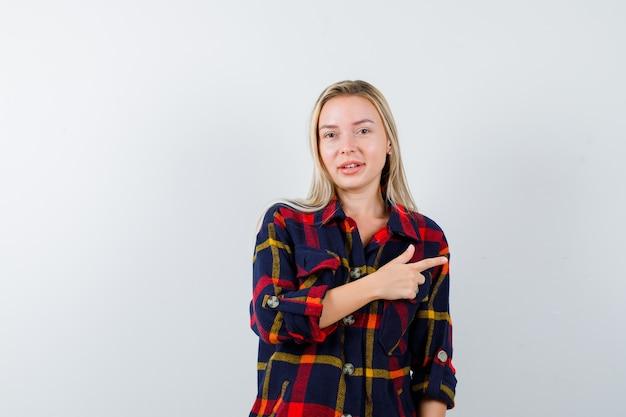 Junge dame im karierten hemd zeigt auf die rechte seite und sieht glücklich aus, vorderansicht.