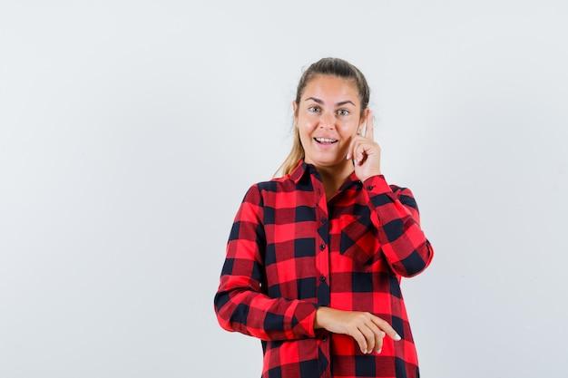 Junge dame im karierten hemd zeigt nach oben, findet ausgezeichnete idee und sieht glücklich aus