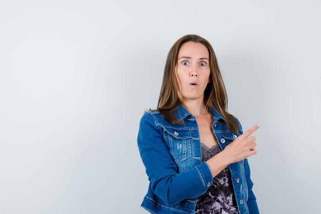 Junge dame im kleid, jeansjacke, die auf die obere rechte ecke zeigt und verängstigt aussieht, vorderansicht.