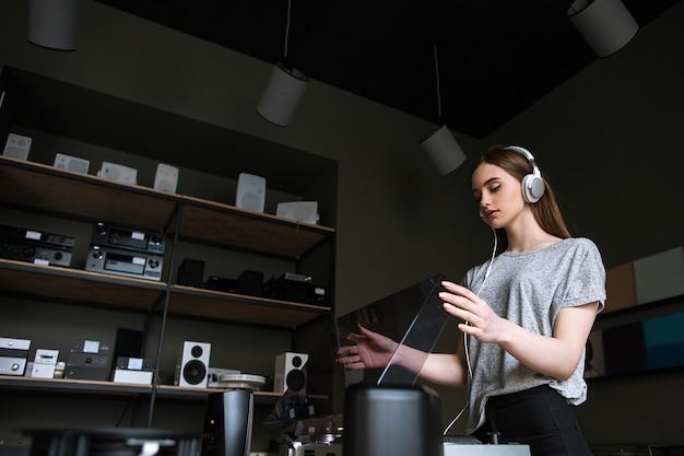 Junge dame im musikladen, die schallplatten auswählt. retro-audio-hören in kopfhörern, moderner hipster-lifestyle