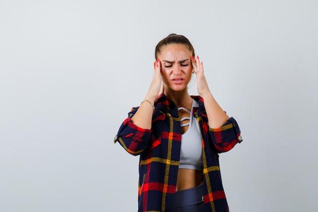 Junge dame im oberteil, kariertes hemd, das sich die schläfen reibt und gestresst aussieht, vorderansicht.