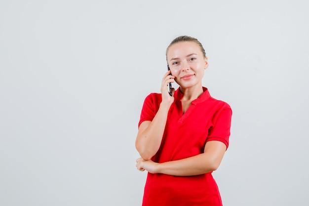 Junge dame im roten t-shirt, das auf handy spricht und fröhlich schaut