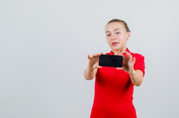 Junge dame im roten t-shirt, das foto auf handy nimmt