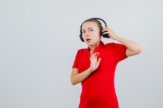 Junge dame im roten t-shirt, die kopfhörer mit stoppgeste abnimmt und ängstlich aussieht