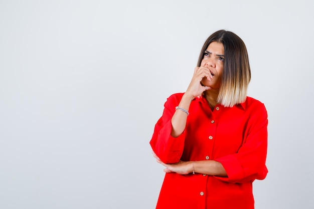 Junge dame im roten übergroßen hemd, die ihre nägel beißt und nachdenklich aussieht, vorderansicht.