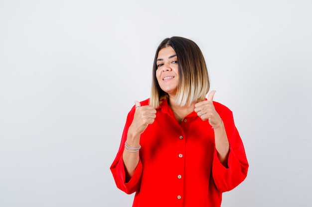 Junge dame im roten übergroßen hemd zeigt daumen hoch und sieht zufrieden aus, vorderansicht.