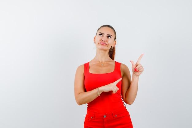 Junge dame im roten unterhemd, rote hose, die auf die obere rechte ecke zeigt und unentschlossen schaut, vorderansicht.