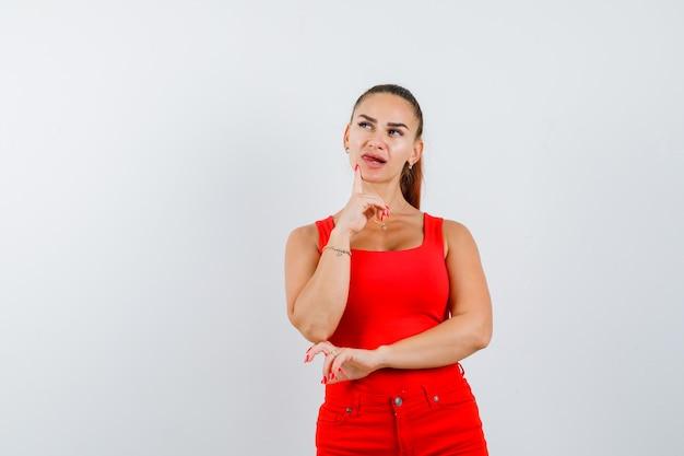 Junge dame im roten unterhemd, rote hose, die finger am kinn hält und ratlos schaut, vorderansicht.