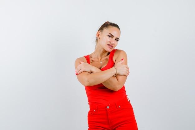 Junge dame im roten unterhemd, rote hose, die sich umarmt und konzentriert, vorderansicht schaut.