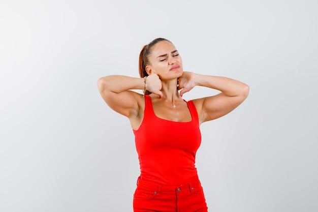 Junge dame im roten unterhemd, rote hose, die unter nackenschmerzen leidet und schmerzhaft aussieht, vorderansicht.