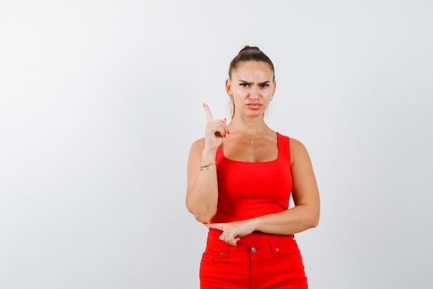 Junge dame im roten unterhemd, rote hose zeigt nach oben und sieht ernst aus, vorderansicht.