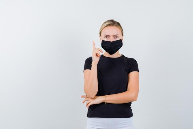 Junge dame im schwarzen t-shirt, maske zeigt nach oben und sieht traurig aus, vorderansicht.