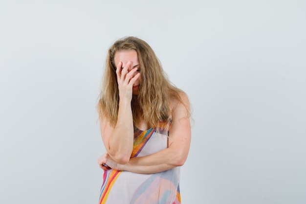 Junge dame im sommerkleid, das gesicht mit hand bedeckt und verzweifelt aussieht