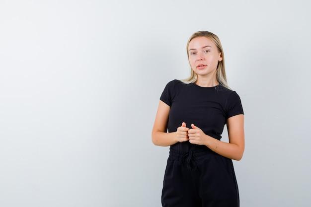 Junge dame im t-shirt, hose zeigt daumen hoch und sieht vorsichtig aus, vorderansicht.