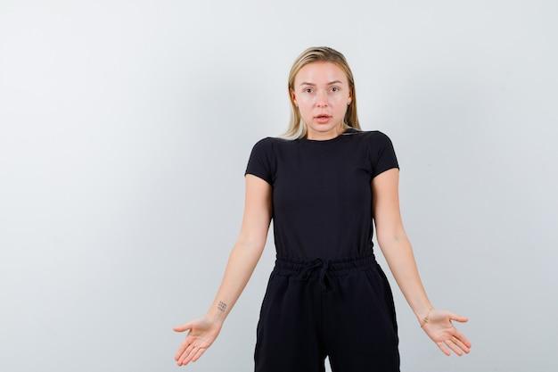 Junge dame im t-shirt, hosen, die handflächen zeigen und vorsichtig schauen, vorderansicht.