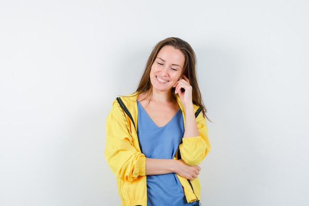 Junge dame im t-shirt, jacke, die in denkender pose steht und optimistisch schaut, vorderansicht.