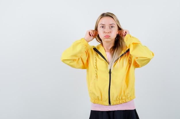 Junge dame im t-shirt, jacke, die lustige geste zeigt, während sie wangen bläst und lustig aussieht