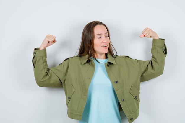 Junge dame im t-shirt, jacke, die muskeln der arme zeigt und stolz schaut, vorderansicht.