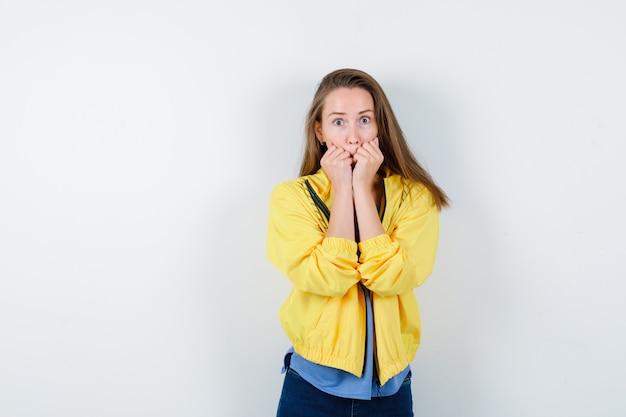 Junge dame im t-shirt, jacke, die sich emotional in die fäuste beißt und verängstigt aussieht, vorderansicht.