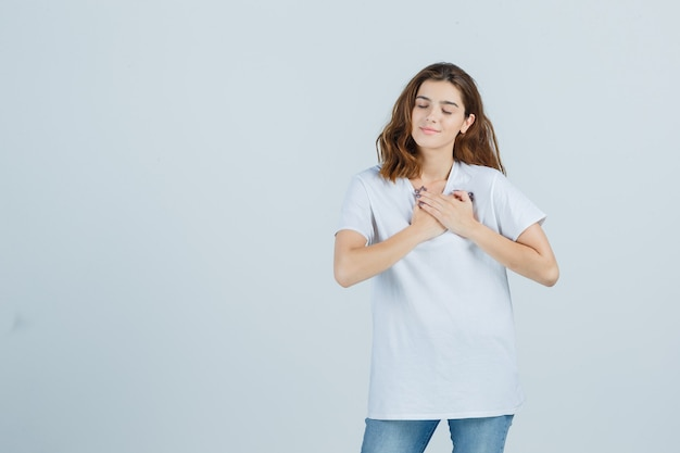 Junge dame im t-shirt, jeans, die betende geste zeigen und hoffnungsvoll, vorderansicht schauen.