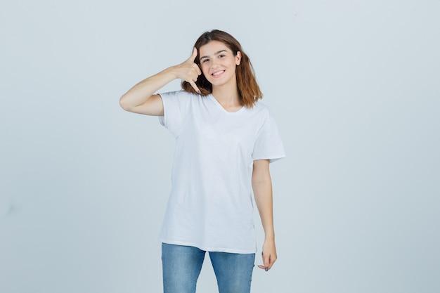Junge dame im t-shirt, jeans, die telefongeste zeigt und freudig, vorderansicht schaut.