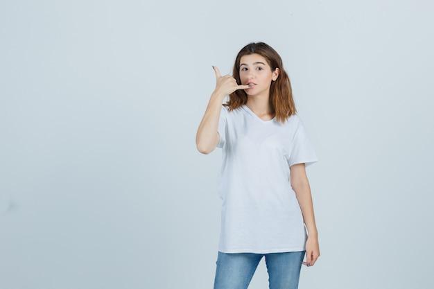Junge dame im t-shirt, jeans, die telefongeste zeigt und selbstbewusst, vorderansicht schaut.