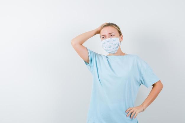Junge dame im t-shirt, maske, die hand auf den kopf hält und vergesslich aussieht