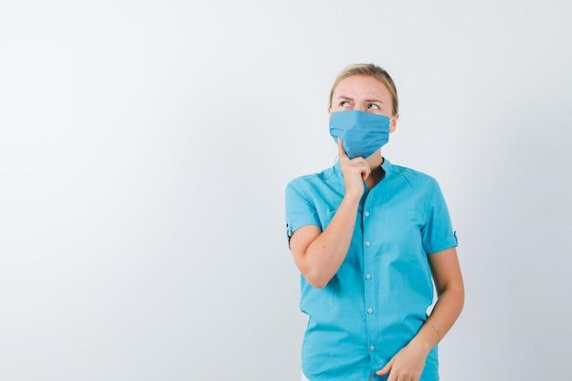 Junge dame im t-shirt, maske, die in denkender pose steht und nachdenklich aussieht