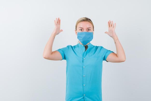 Junge dame im t-shirt, maske hält die hände in kapitulationsgeste und sieht ängstlich aus