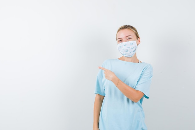 Junge dame im t-shirt, maske nach links zeigend und selbstbewusst aussehend