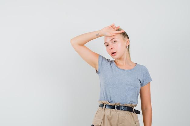 Junge dame im t-shirt und in der hose posiert mit der hand auf der stirn und sieht nett aus