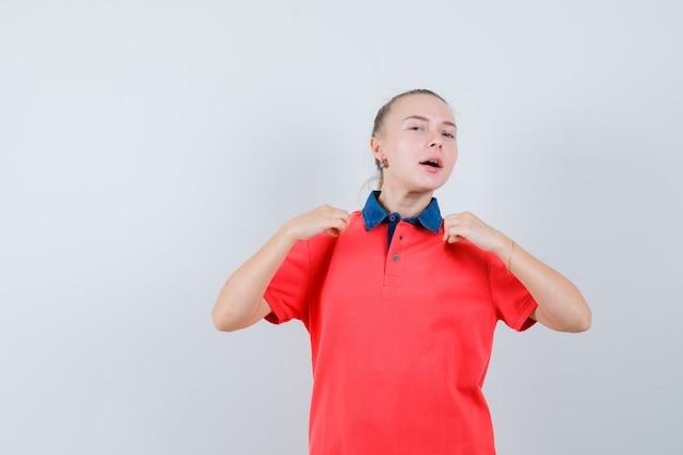 Junge dame im t-shirt zieht ihr t-shirt und sieht stolz aus
