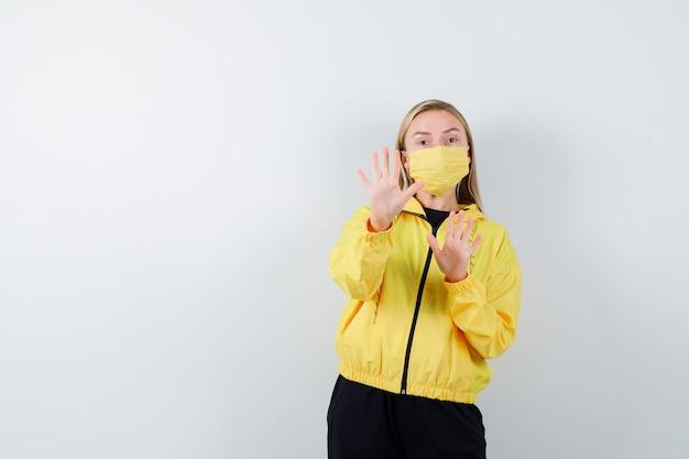 Junge dame im trainingsanzug, maske, die stoppgeste zeigt und ängstlich schaut, vorderansicht.