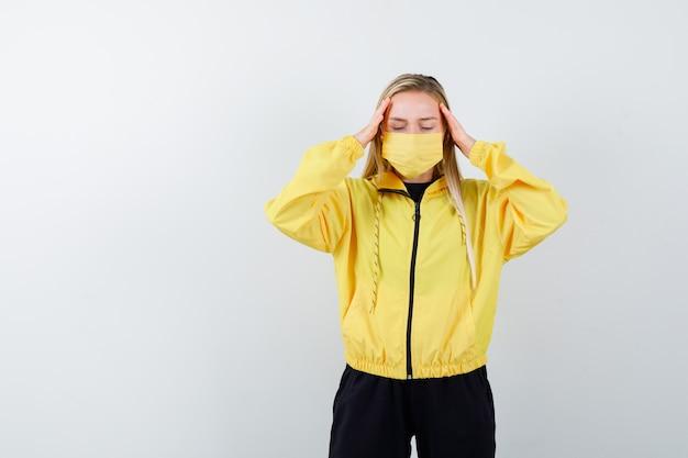 Junge dame im trainingsanzug, maske, die unter kopfschmerzen leidet und müde aussieht, vorderansicht.