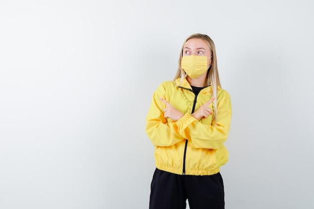 Junge dame im trainingsanzug, maske zeigt nach links und rechts und sieht zögernd aus, vorderansicht.