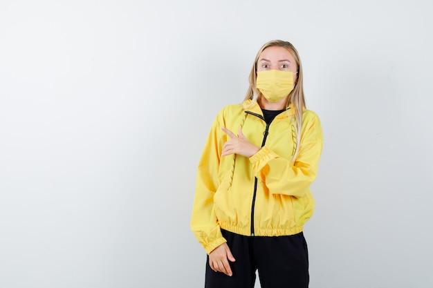 Junge dame im trainingsanzug, maske zeigt nach links und sieht ängstlich aus, vorderansicht.