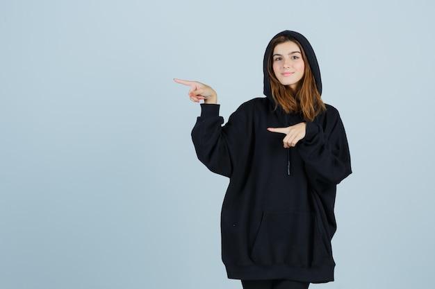 Junge dame im übergroßen kapuzenpulli, hose zeigt auf die linke seite und sieht selbstbewusst aus, vorderansicht.