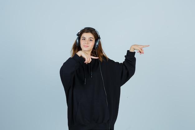 Junge dame im übergroßen kapuzenpulli, hose zeigt auf die rechte seite, während sie musik mit kopfhörern hört und charmante vorderansicht sieht.