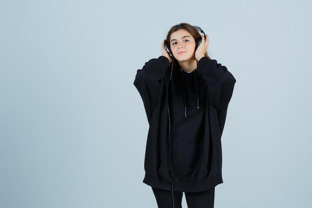 Junge dame im übergroßen kapuzenpulli, hosen, die hände auf kopfhörern halten, während sie musik hören und positiv, vorderansicht schauen.