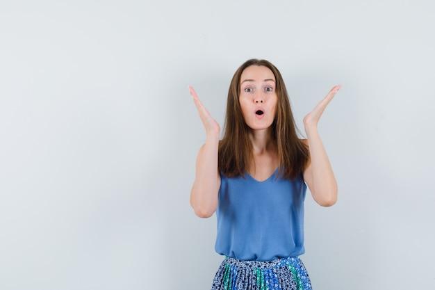 Junge dame im unterhemd, rock hält hände erhoben und sieht überrascht aus Kostenlose Fotos