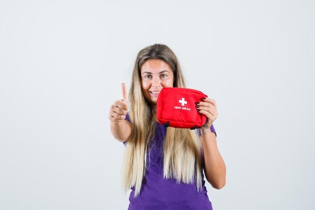 Junge dame im violetten t-shirt, das erste-hilfe-kit hält, zeigt daumen hoch und schaut fröhlich, vorderansicht.